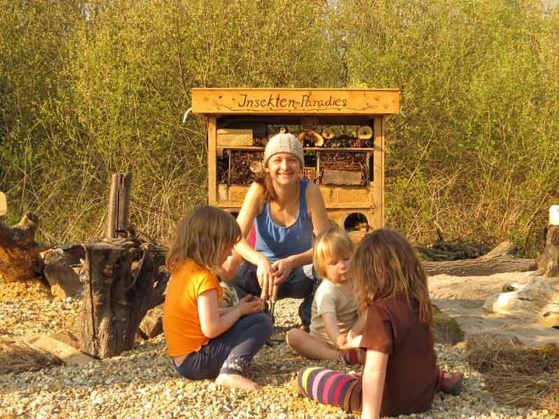 drei Kinder und Frau vor fertiger Nistwand im Sonnenschein